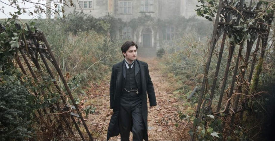 Daniel Radcliffe in 1900s British period clothing stands center, between falling over gates covered in overgrown plants