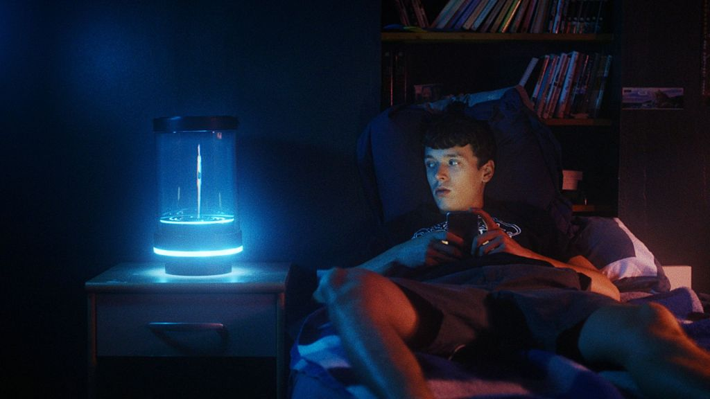 A teenage boy sits on a bed in a dark room, looking to his right at a tube containing an AI girl.