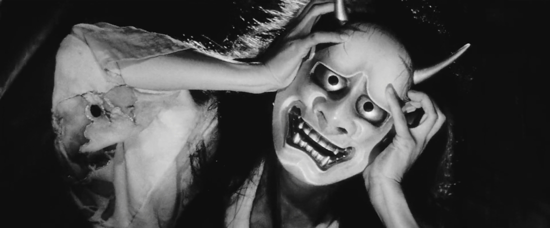 Image is from the film 'Onibaba'. A woman tries to pull a grotesque mask from her face. The image is in black and white.