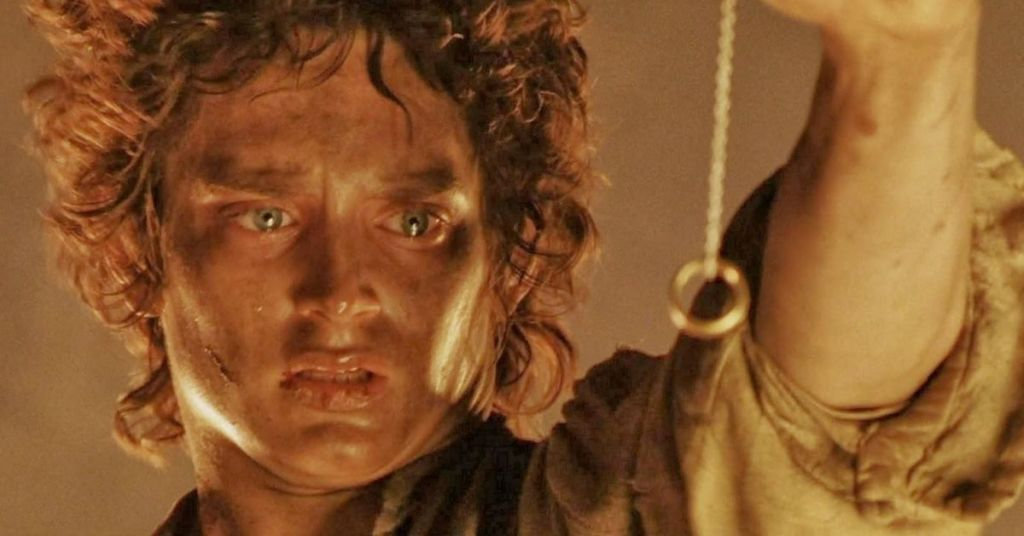 Lord of the rings trilogy image - Frodo Baggins has the ring on a chain, staring at it. he's got tears in his eyes and cuts on his face
