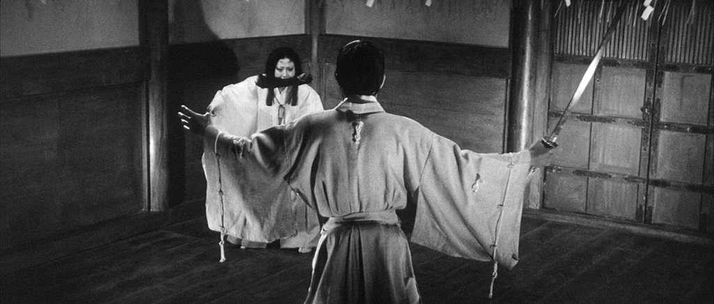 This image is from the film Kuroneko. A samurai brandishes a sword at a woman. The image is in black and white.
