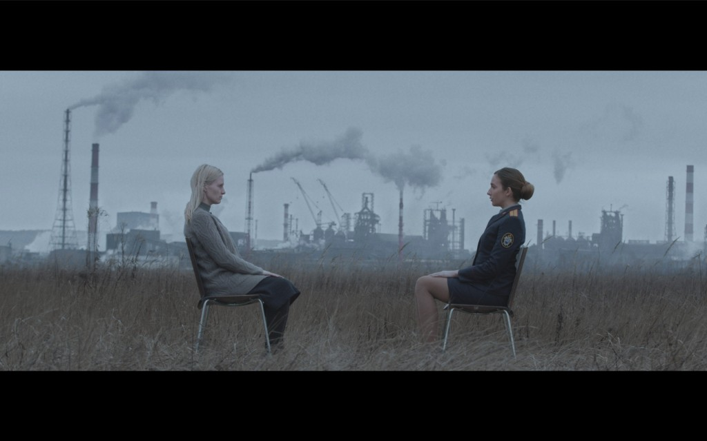 Still from Sulphur: Two women are sitting in a field. The woman to the left is blonde in a grey cardigan while the brown-haired women on the right is a policewomen in uniform. In the background are factories with smoke going into the sky above.