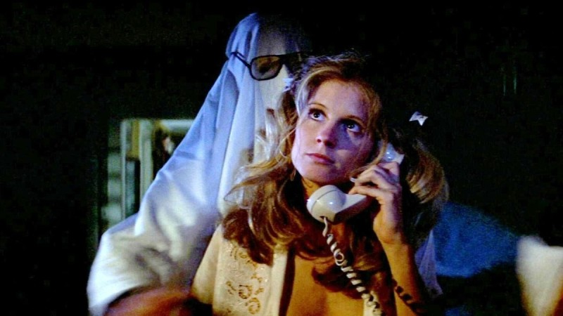 Image is from Halloween (1978). A woman is on the phone, unaware that someone wearing a white sheet over their head is about to grab them