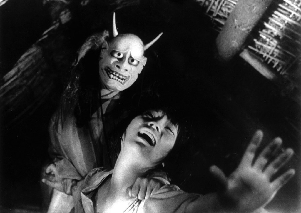This image is from the film Onibaba. A woman wearing a grotesque mask pulls another woman across a room. The image is in black and white.