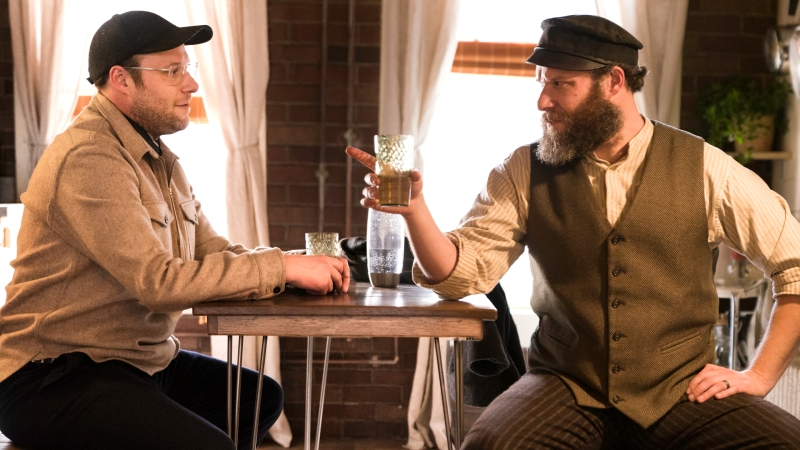 This image is from 'An American Pickle'. Ben and Herschel (both played by Seth Rogan) sit opposite one another. Herschel (right) raises and a glass and points at Ben.
