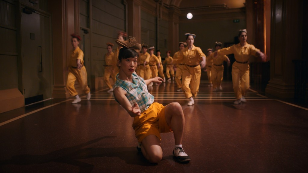 A woman in a checkered blue top and yellow shorts kneels on the ground balancing a brown shoe on her head. In the background is a chorus of dancers in yellow work uniforms. From 'Cinderella Games'.