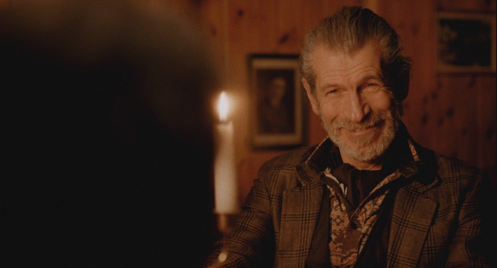 An elderly man- wearing a formal, floral shirt and a tweed jacket- smiles to someone off screen at a candlelit dinner. From 'Brothers Again'