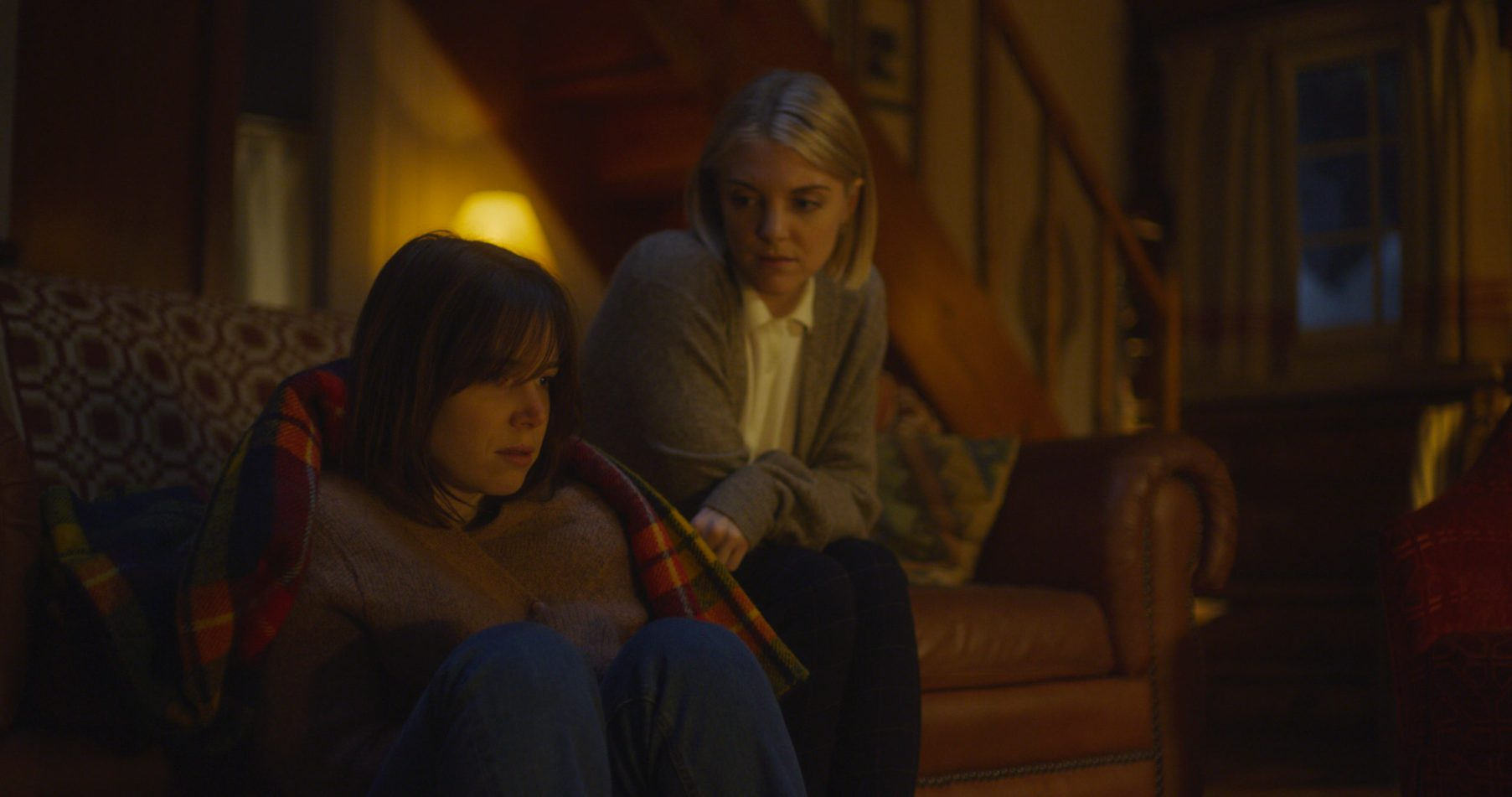 Emily comforts Rowan by the fireplace.