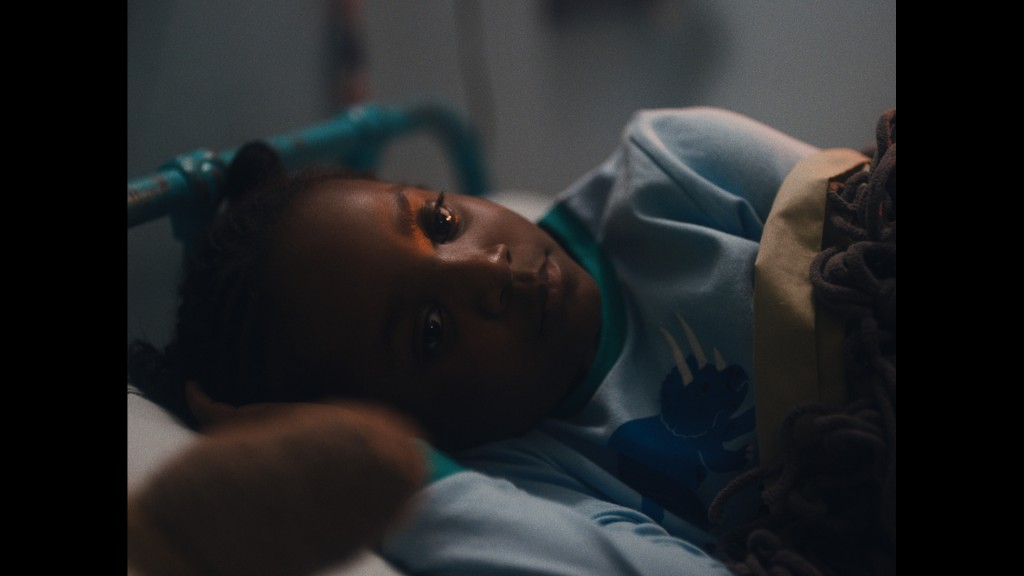 Still from Dawn in the Dark: Dawn, a young child is tucked into bed. Her dark skin is lit by her nightlight, covers wrapping her up.