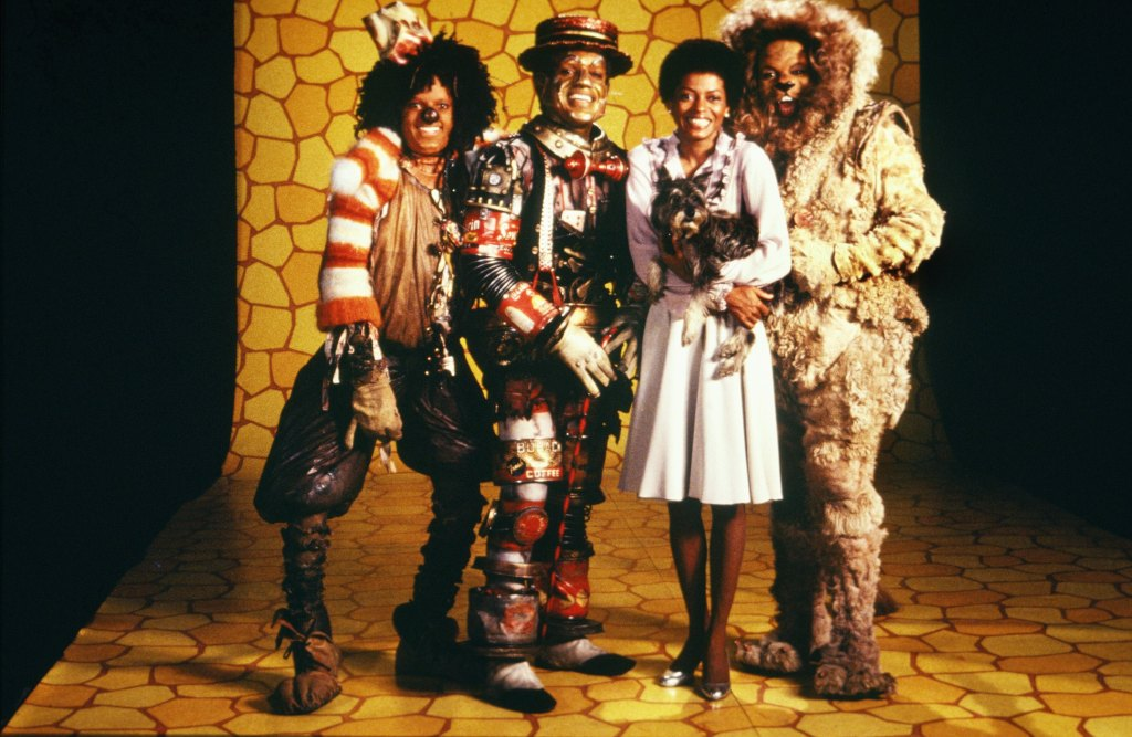 The Wiz Image - Diana Ross as Dorothy Gale with her grey dog in her arms, Michael Jackson as Scarecrow Nipsey Russell as Tin Man and Ted Ross as Cowardly Lion. they are all standing on the yellow brick road set