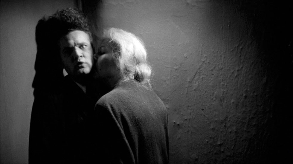 Black and white; A white man with a curly flat top haircut is kissed on the neck by a white woman with light blonde hair
