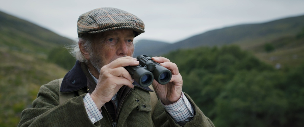 An elderly man wearing a famers jacket and flatcap, peers over a pair of binoculars- standing in a vast green valley. From 'Ghillie'