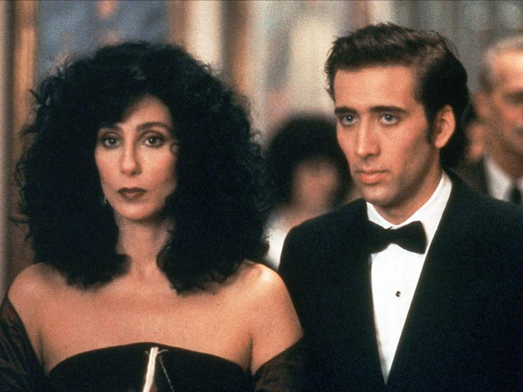 Moonstruck Image - cher and nicholas cage are looking forward. cher has volumous black curly hair and a black dress. nicholas cage has a suit and bow tie on. they look serious