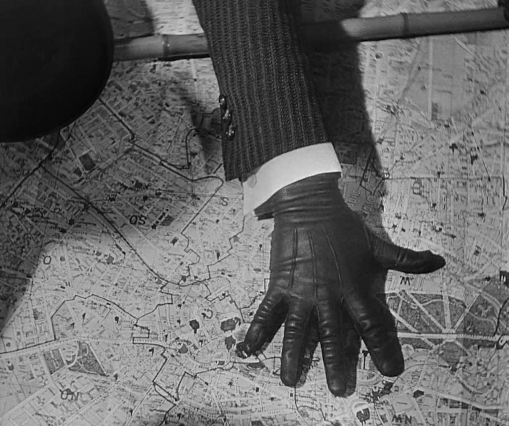 A black, gloved hand appears on top of a map.