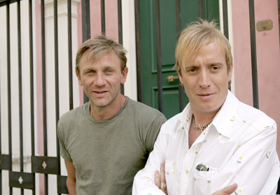 Enduring Love Image - Daniel Craig is wearing a green t shirt and Rhys Ifans  is standing beside him in a white shirt and necklaces. they are stood in front of black gating with a pink wall behind