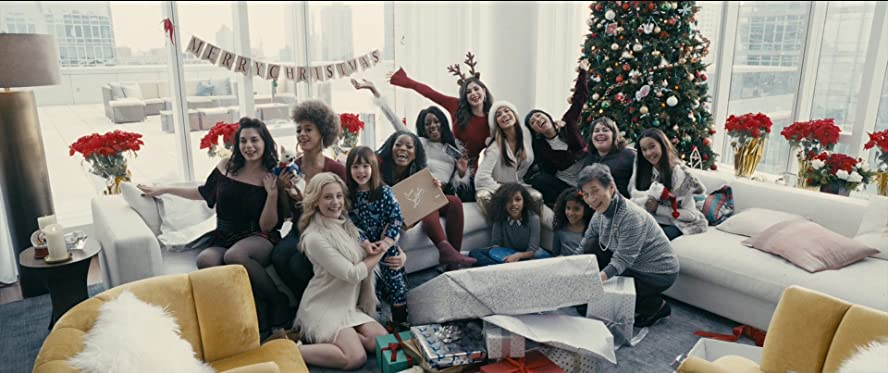 Hustlers Image - all the girls are on the pristine white couches in front of the huge christmas tree. presents cover the floor. they are all looking to the camera for the photo