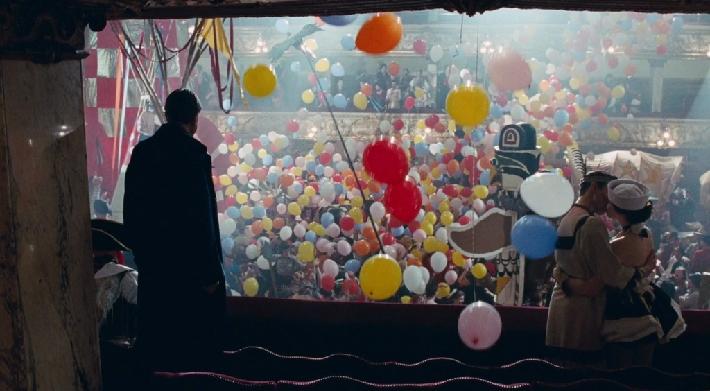 Phantom Thread Image - Reynolds stands in a long coat, he is looking out at the New Years celebration from a theatre balcony. they clock has just struck midnight and balloons are falling all around. To Reynolds right, a couple are kissing.