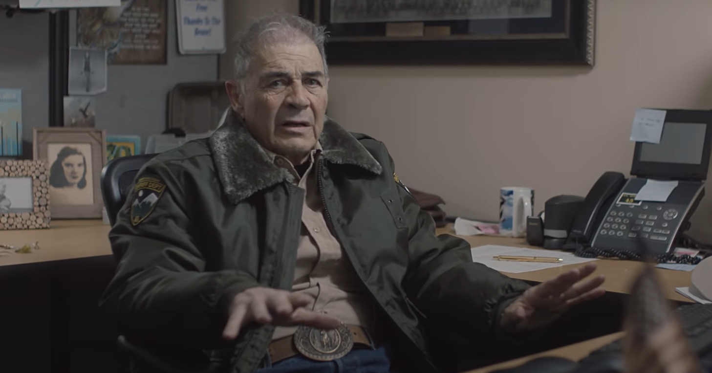 Robert Forster's Sheriff Hadley sits, worried, at his desk.