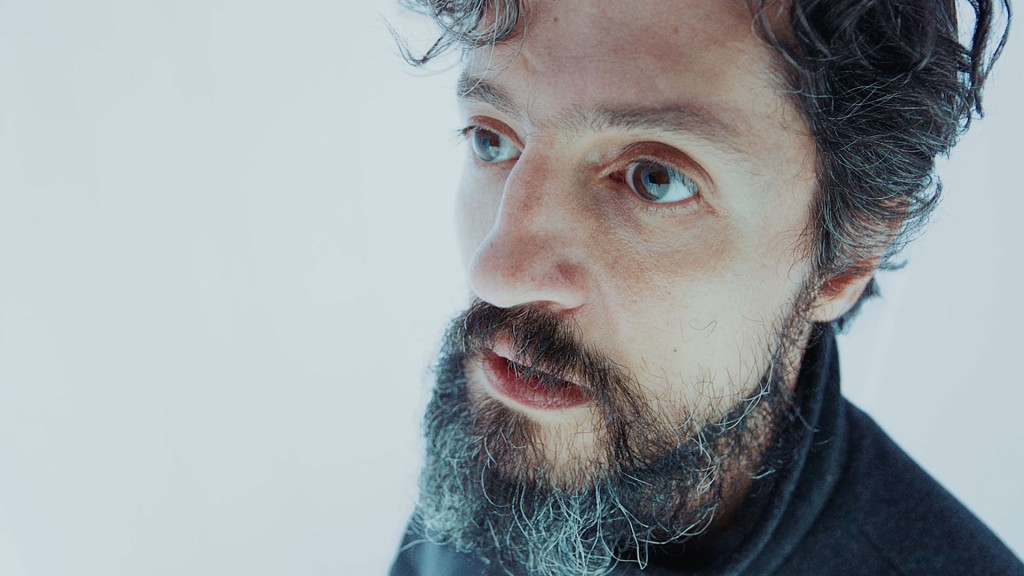 A bearded man stares into space with a daunted look, with a glaring white background behind him. From 'Instant Doctor'