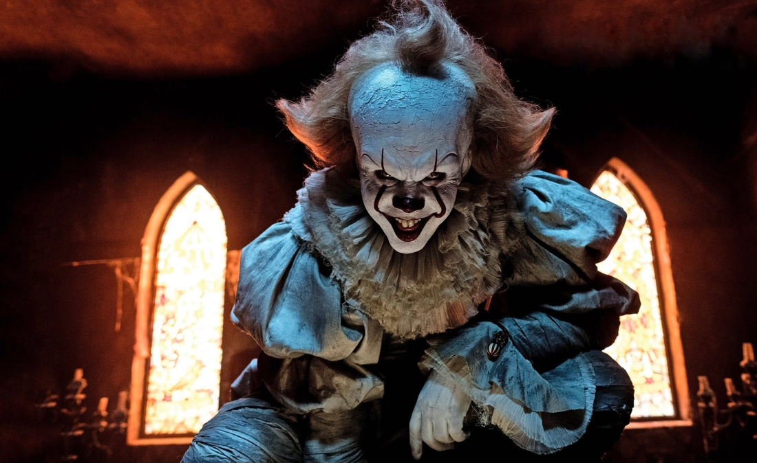 Pennywise the clown smiles creepily in blue lighting with two windows glowing behind him
