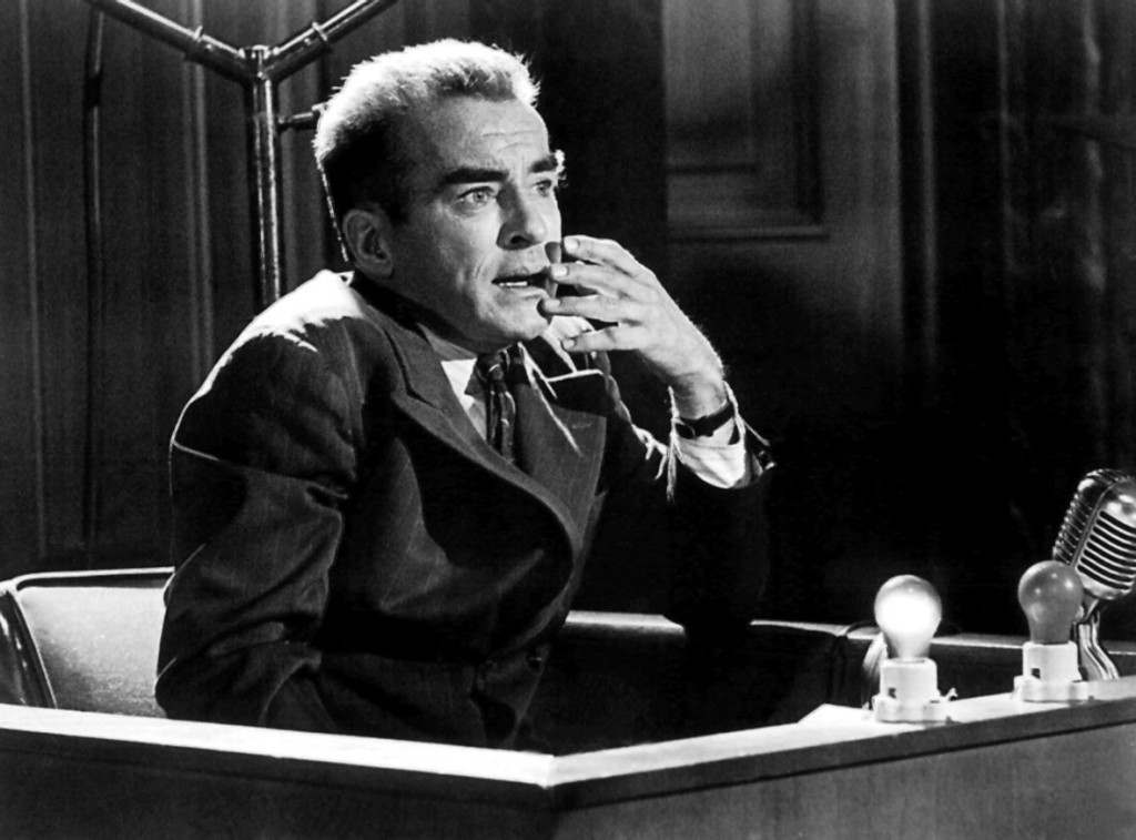 A black and white image of a man sat in a witness box. He is wearing a suit and appears to be talking. His hand is by his face.