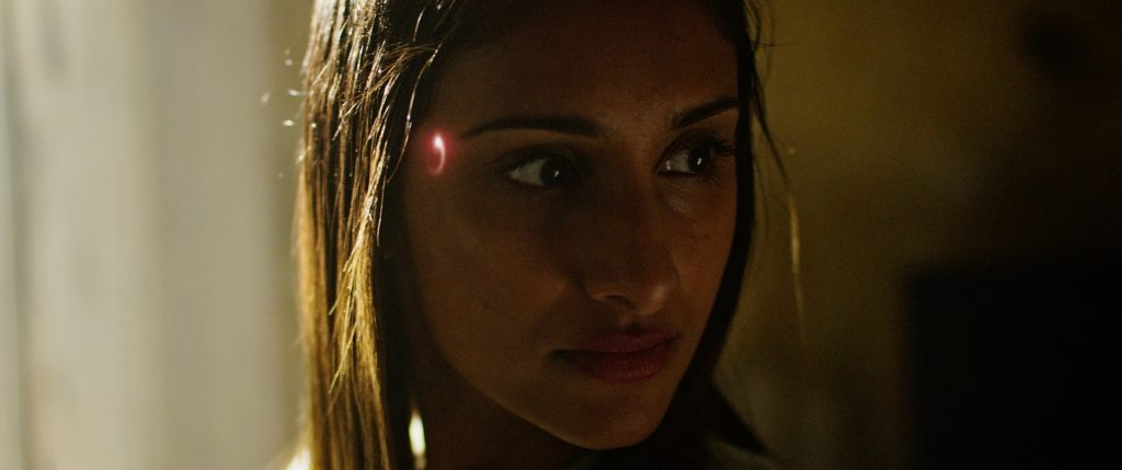 A female android, with a glowing symbol to the right of her right eye, glances at something off screen in a poorly lit room. From 'Muse'