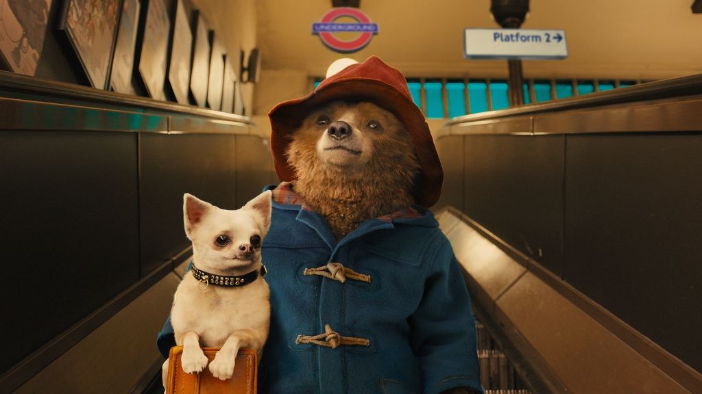Paddington image - paddington the shaggy brown bear is going down an escalator on the london underground. wearing a red hat and blue coat, a small white dog is on his suitcase