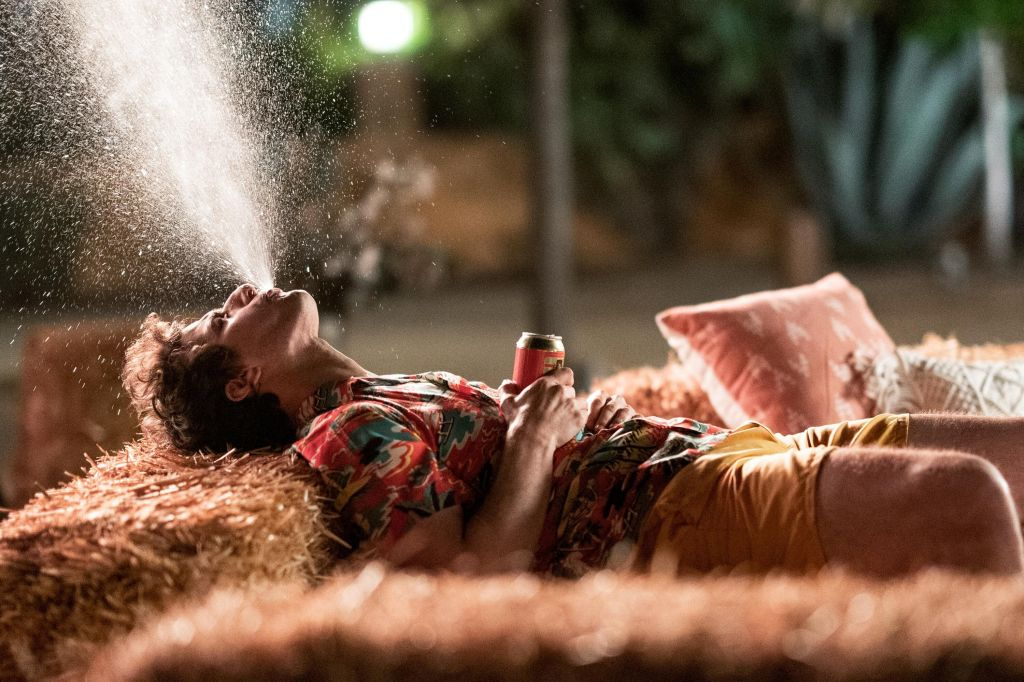 This image is from 'Palm Springs' (2020). Nyles (Andy Samberg) lies back on a hay bale and sprays water into the air.
