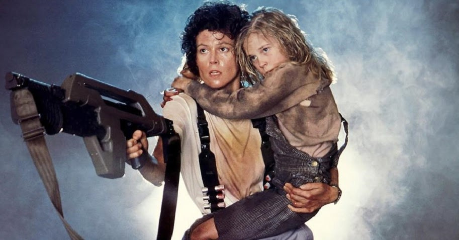 Sigourney Weaver holding a girl in movie still from Aliens.
