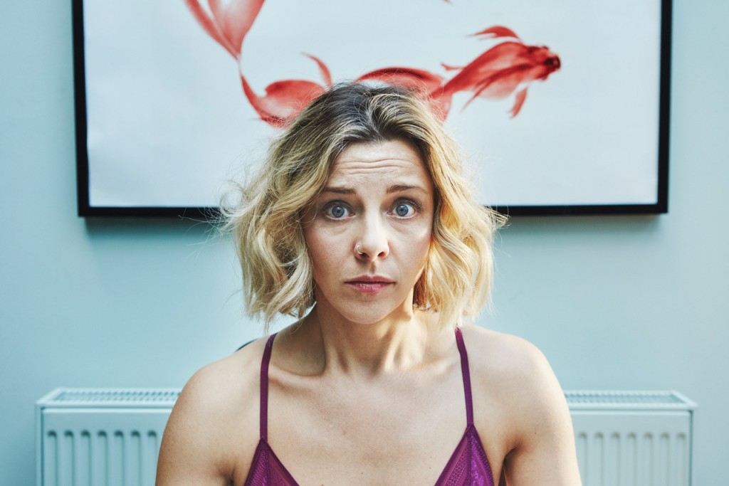 Still from End-O: Jaq has a blonde bob with dark brown roots, she is wearing a purple bra and staring into the camera with a terrified face. She is standing in a lounge with a picture of red fish against a white background not he wall behind.