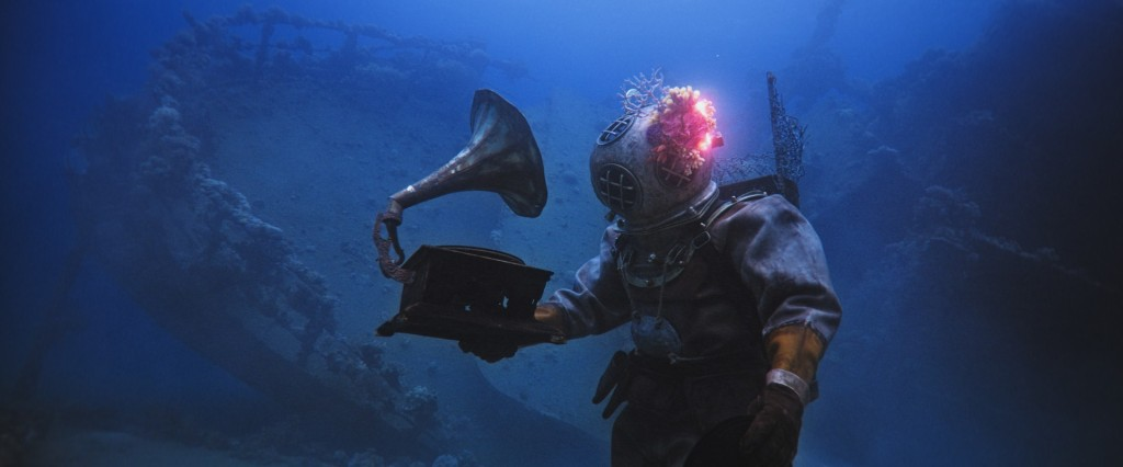 In the dark depths of the sea, in front of a wreckage, a deep-sea diver in a 20th century diving suit holds up a vinyl player. From 'The Coral Guardian'.