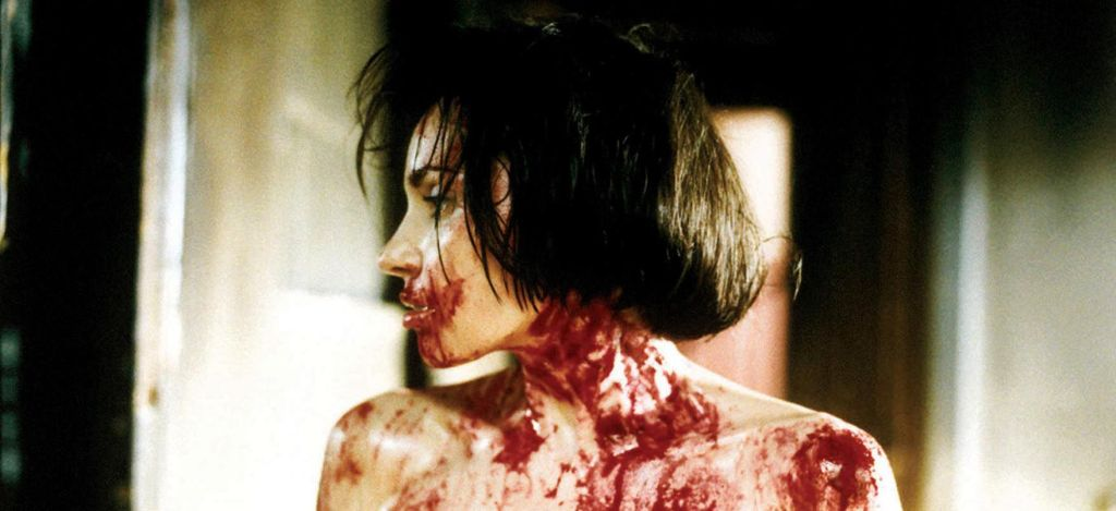 Close up of a white woman with a black bob haircut in profile view. Her mouth, neck, and bare shoulders are smeared with blood.