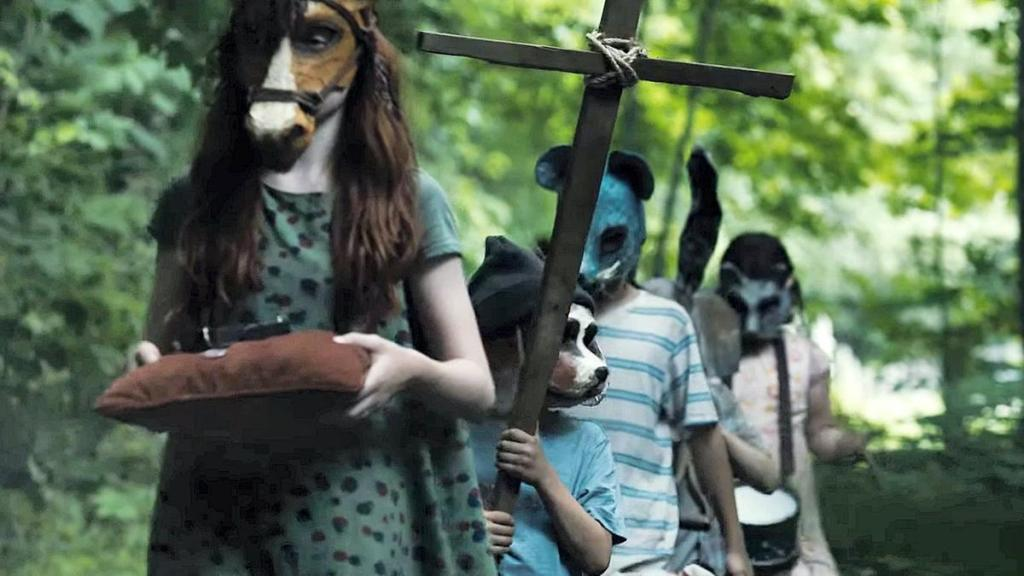 5 children wearing various animal masks walk in a line in the woods. The first holds a pillow, the second a homemade cross, and the last a drum.