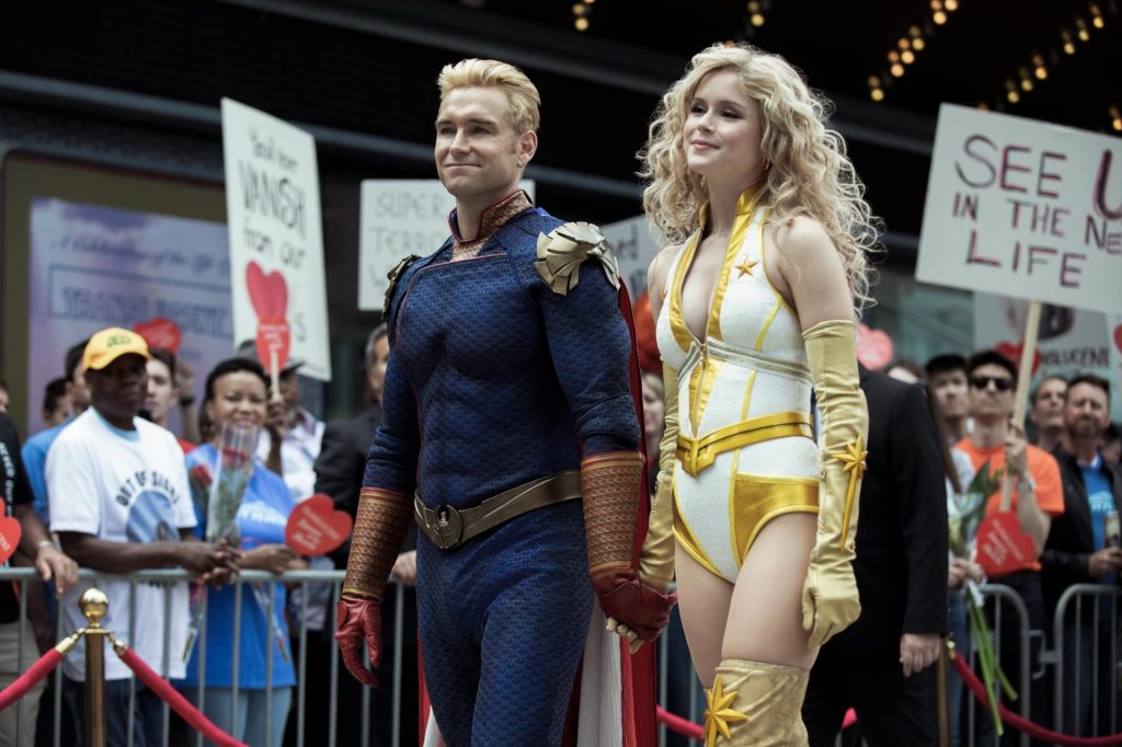 Homelander (Antony Starr) and Starlight (Erin Moriarty) walk through a crowd of supporters.