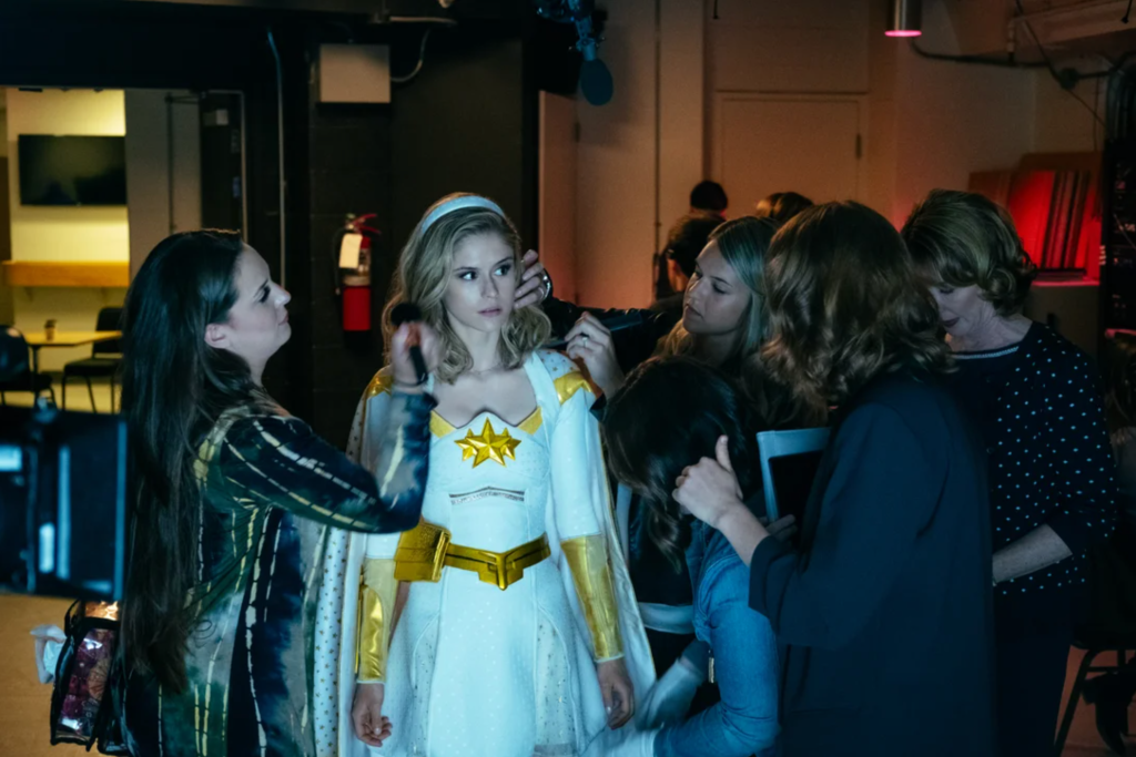 Starlight (Erin Moriarty) surrounded by people who are fixing her hair before she gets on stage.