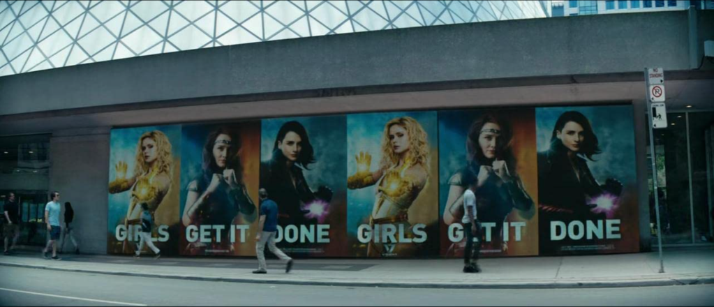 """Images of Starlight, Stormfront and Queen Maeve are plastered on the side of a bus stop with the slogan: """"Girls Get It Done."""""""