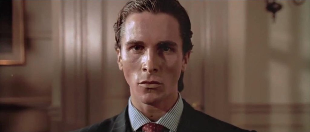 Patrick Bateman stands against a blank wall and looking similarly one-note at the camera, with sweat-drenched skin and an intense stare