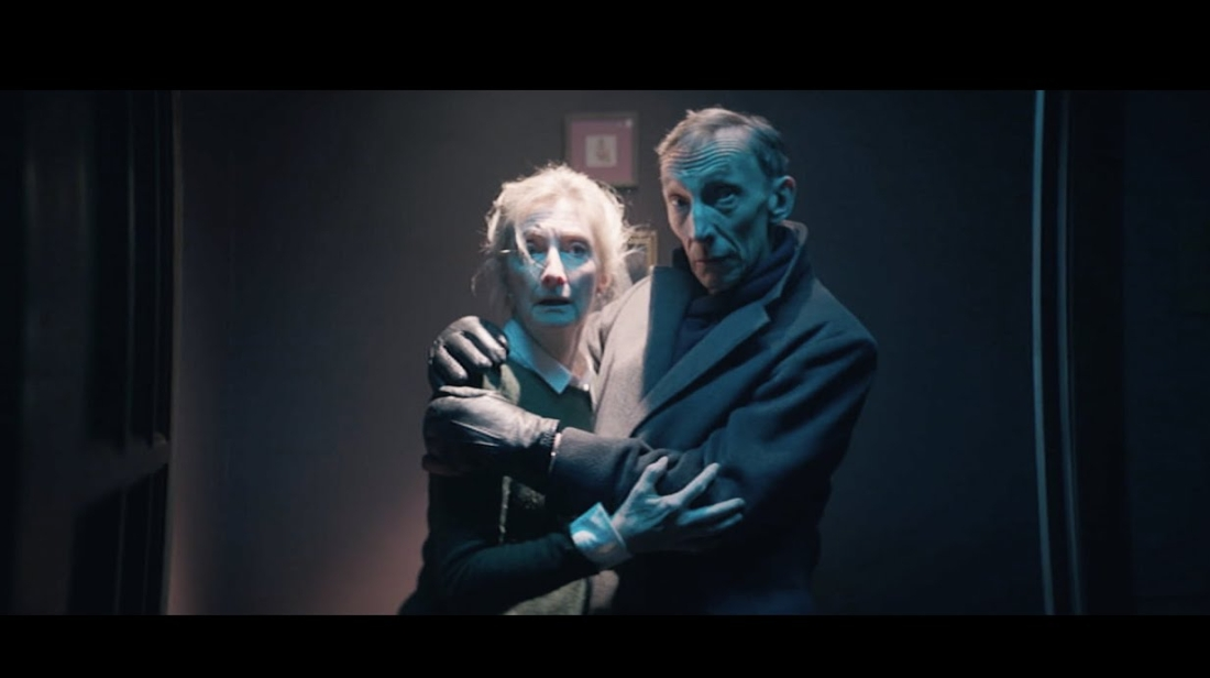 An elderly couple (played by Shelia McCarthy and Julian Richings) hold each other in panic. They're standing in a dimly lit hallway. The woman has dishvelled white hair and the man has thin receeding hair. The man looks calmer than the woman, who is more alarmed by what she is looking at.