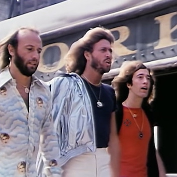 "Maurice, Barry, and Robin Gibb walking down the street in their ""Stayin' Alive"" music video."