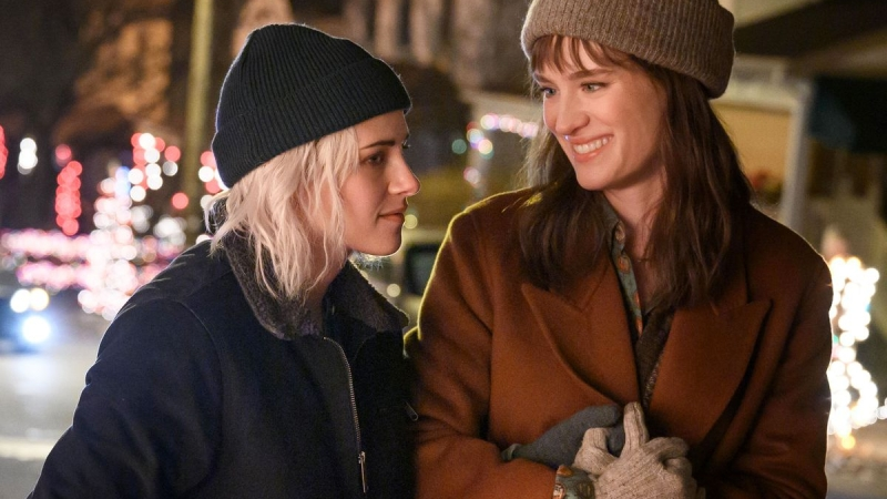 Image from the film Happiest Season. Two women walk down a street covered in Christmas lights. One looks lovingly at the other.