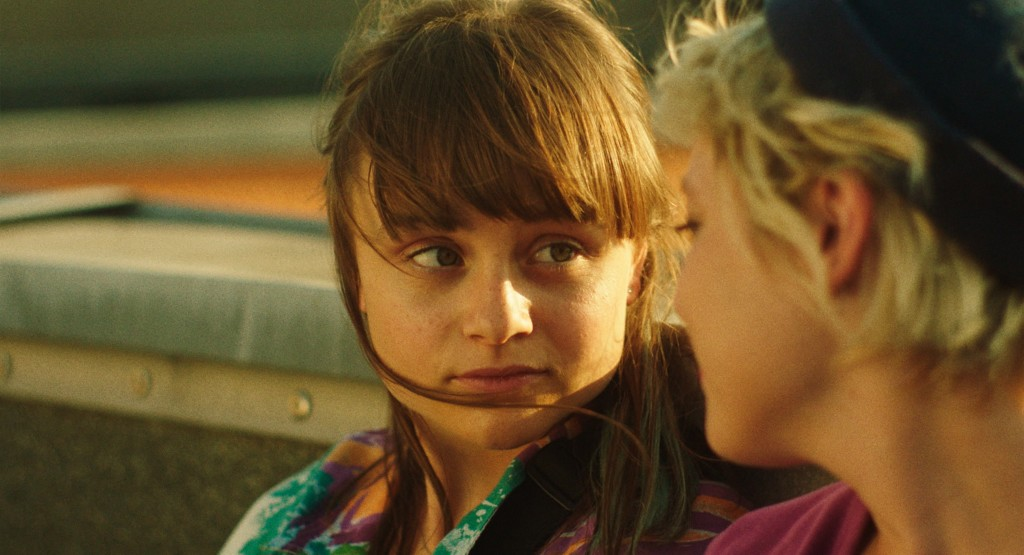 Nora, with brown hair and a fringe in a multicoloured shirt stares at Romy, waring a black beanie and maroon t shirt