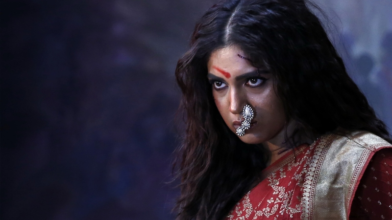 Image from the film 'Durgamati' (2020). A young woman is dressed in a red sari and glares menacingly in the distance.