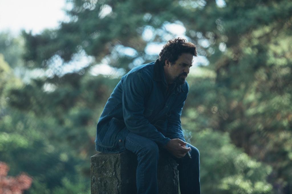Mark Ruffalo sits on a tree stump smoking.