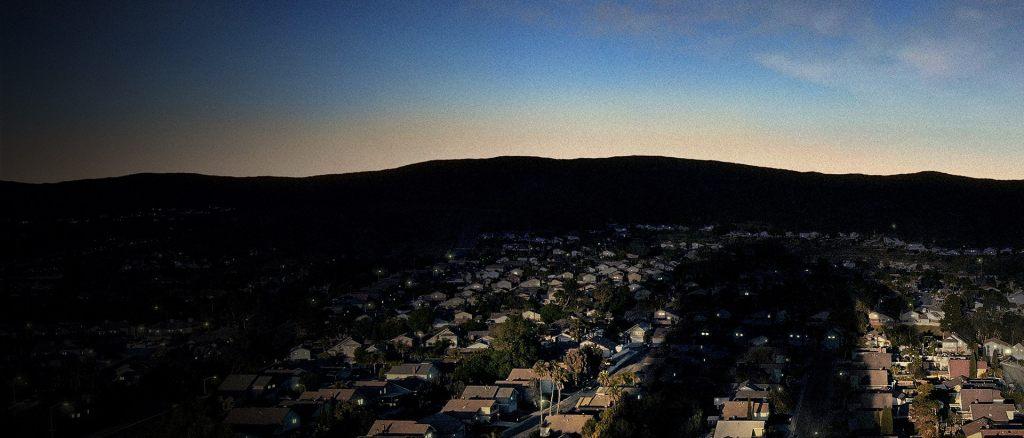 An establishing shot of a light blue sky before sunset overlooking a suburb.