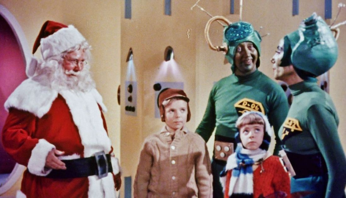 Santa smiles alongside two martians and two human children.