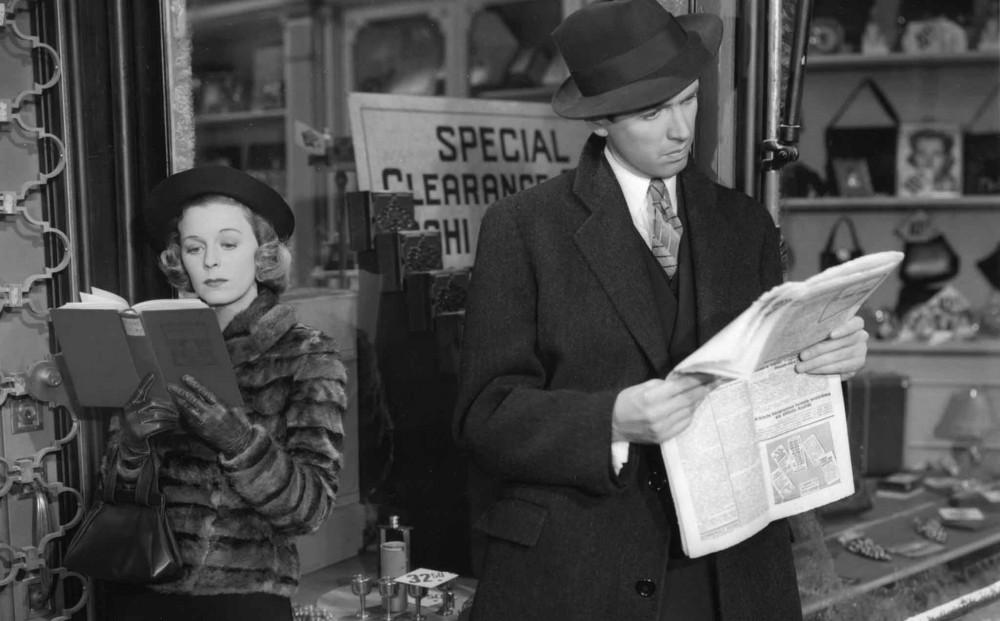 James Stewart and Margaret Sullivan standing back to back reading.