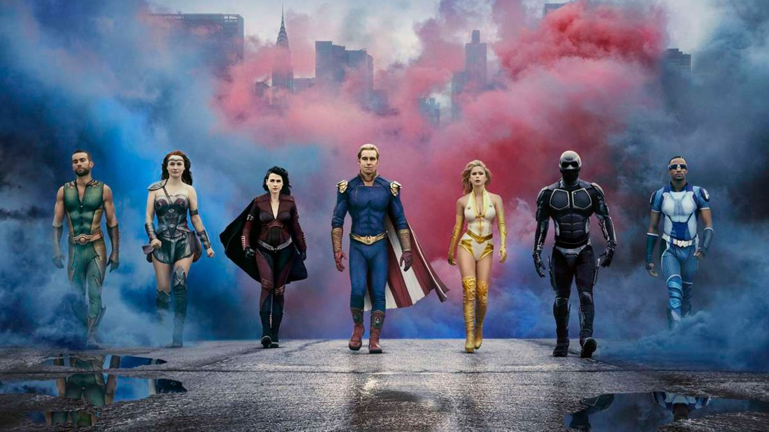 Image from the TV Show 'The Boys'. A group of seven superheroes walk towards the camera. The backdrop behind them is a city covered by red and blue smoke.