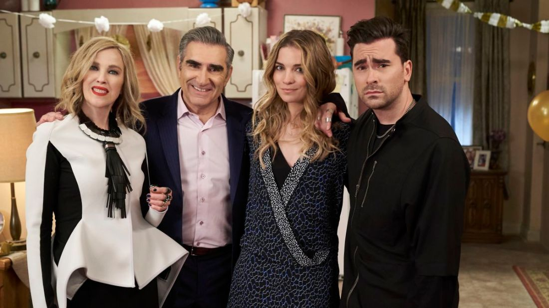 Image is from the TV Show 'Schitts Creek'. The Rose family post for a family photo at a birthday party.
