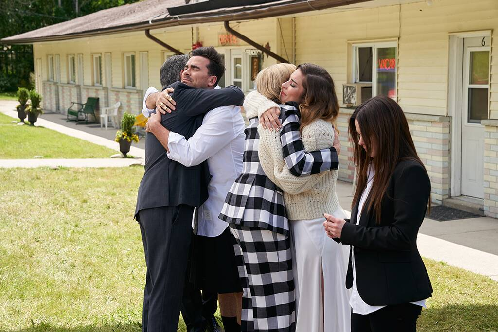 Image is from the TV Show 'Schitts Creek'. The Rose family hug one another outside of their home.