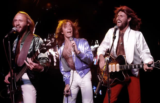 Maurice, Robin, and Barry Gibb singing in concert.